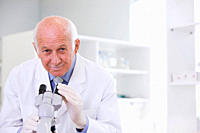 Male scientist using microscope in laboratory, portrait