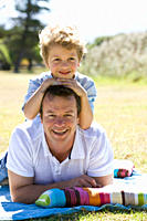 Father and son 8_9 laying on lawn, portrait