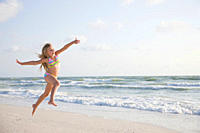 USA, Florida, St. Pete Beach, Girl 8_9 in bikini jumping on beach