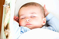 Portrait of a sleeping baby lying in his cradle at home