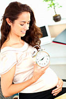 Pregnant businesswoman holding an alarm clock and looking at her belly in her office sitting at her desk