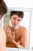 young man putting some shaving foam looking his face in the mirror standing in the bathroom