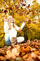 teenage girl in park playing with autumn leaves