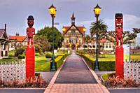 Rotorua Museum entrance pathway lined by lamps and Maori wooden carved figures, dusk, Government gardens, Rotorua.