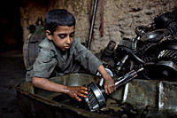 Mohammed, 10, cleans automobile parts with kerosene at an auto repair shop in the Pia Minara neighborhood of the north_western city of Herat The avera...