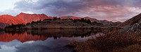 Panoramic image of the Colorado Rocky Mountains reflecting in Pass Lake at sunset. Pass Lake is located directly on the continental divide