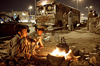 Children from Afghanistan making tea, by the side of a road, in Karachi, Pakistan They scavenge recyclable materials at day and make a living by selli...