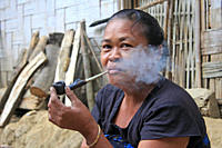 An elderly woman from ethnic community smokes a pipe Tidu in Bandarban, Bangladesh December 4, 2009