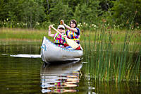 A girl and a woman in a canoe on the island of Norrbyskaer, Vaesterbotten, Sweden, Europe