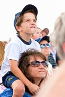 Young boy on mom's shoulders watches the skys during air show at NAS Jacksonville, Florida