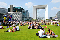 Lunch on the grass, the Grande Arche, buildings of the business sector Paris La Défense, Paris, France.