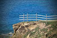 Unfinished fence on cliff above ocean