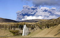Distant view of the Seljalandsfoss waterfall with the ash plume of the Eyjafjallajokull eruption in the distance, near Hella, southern Iceland, Icelan...