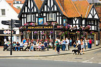 England, North Yorkshire, Scarborough. People sitting outside the Newcastle Packet pub on Sandside.