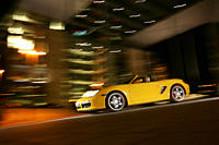Car, Porsche Boxster S, model year 2004_, yellow, Convertible, open top, driving, diagonal from the front, frontal view, side view, City, at night