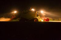 Combine Harvester, harvesting corn at night with lights on, Lower Saxony, Germany