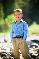 Outdoor portrait of young boy looking at camera and smiling wearing blue shirt and khaki pants