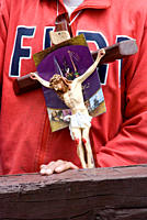 Close up shot of unrecognizeable man holding cross and Christ figureine, Semana Santa Catholic Easter celebrations, Quito Old Town, Ecuador, South Ame...