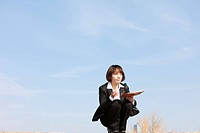 Businesswoman crouching holding diary and pen, Midsection