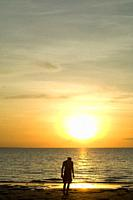 A man in front of the sunset on Mindil Beach in Darwin in the Northern Territory of Australia
