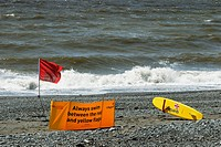 Red warning flag with RNLI rescue surfboard on a deserted beach with rough sea, Aberystwyth, Wales