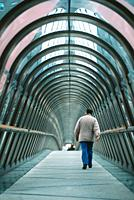 A man walks alone through the tunnel of a covered skybridge in La Defense, Paris, France