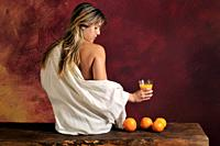 half-naked young woman witht oranges and orange juice