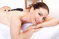 Woman having a hot stone treatment, smiling, portrait