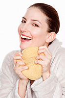 Woman in bathrobe holding sponge, smiling, portrait