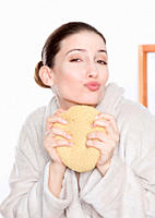 Woman in bathrobe holding sponge and pouting, portrait