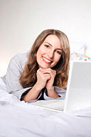 Woman lying on bed with laptop, smiling, portrait