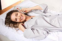 Woman lying on bed and talking on the phone