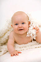 Baby boy 6_11 months lying on bed, smiling, looking away