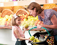 Mother and daughter buying fruit in grocery store