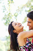 Laughing woman hugging husband outdoors