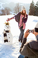 Man taking picture of girlfriend and snowman