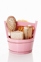 Basket with sponges and brushes on white background