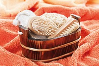 Basket with sponges, brushes and pumice on towel