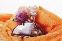 Bath oil with flower on towel