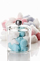 Cotton balls in container on white background