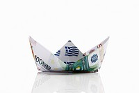 Origami paper boat of euro notes on white background