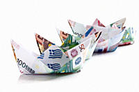 Origami paper boats of euro notes on white background