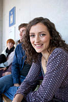 Germany, Leipzig, Woman smiling with students in background