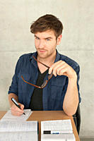 Germany, Leipzig, Young man writing and studying, portrait