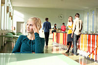 Germany, Leipzig, Woman sitting in hallway, students standing in background