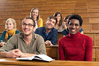 Germany, Leipzig, Group of university students studying in classroom, smiling