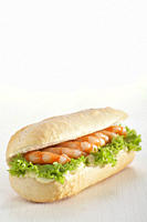 Baguette roll filled with prawns against white background
