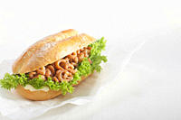 Baguette roll filled with shrimp against white background