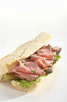 Baguette filled with slices of roast beef.