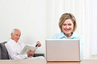Woman using laptop with man sitting in background